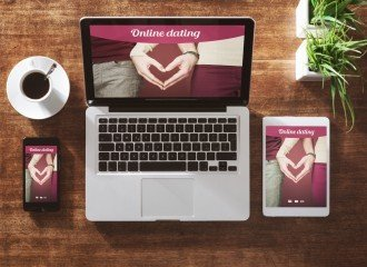 Online dating website on a laptop display, hardwood desktop on background